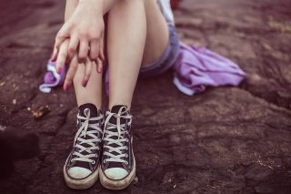 Legs and shoes of teen sitting outside